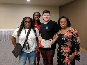 Patrick Foster standing with his WI Promise councilors. Patrick is holding a certificate for completing a Promise training.